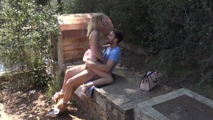 Blonde Aria Logan bends over outdoors